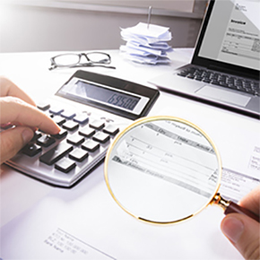 Hand using calculator, magnifying glass, glasses laptop on table looking closely at paper