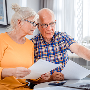 Worried senior couple checking bills using laptop and papers at home