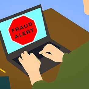 Computer on table, hands typing on keyboard, black letters saying fraud alert on a red octagon