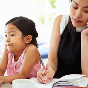 Woman writing in book with young child sitting next to her