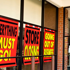 Store windows with signs that say store closing, going out of business,, and everything must go