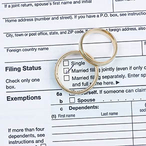 Wedding rings with United States tax form 1040 over filing status with married checked in middle of one ring