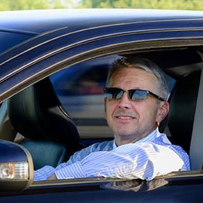 Man in drivers seat of car with windows down and wearing sunglasses