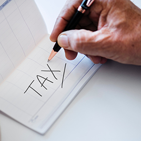 Man writing the word tax in calendar book