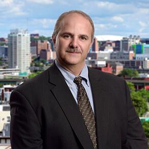 Joe Chemotti headshot partner of Dannible & McKee with Syracuse, New York skyline in background