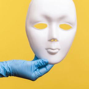 Medical glove holding white full face mask