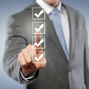 Square image of man in business suit pointing at checkmarks in a list