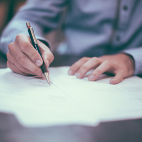 Man using a pen signing papers