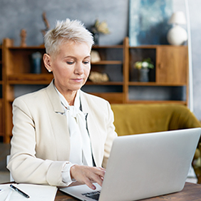 Lady with white suit and short gray hair typing on laptop