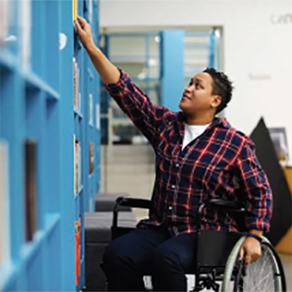 Person in wheelchair reaching for object on high shelf