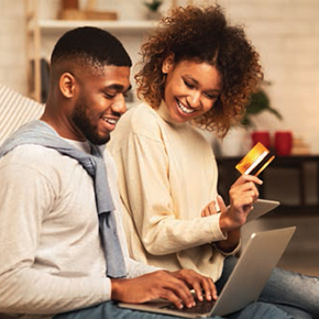 Couple sitting together on computer, woman is holding a credit card
