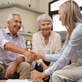 Woman shaking hands with older couple after signing a paper