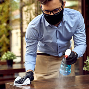 Waiter spraying and wiping down a table