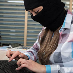 Woman wearing ski mask cyberattacking computer