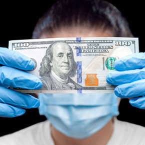 Person wearing face mask and gloves holding $100 bill in front of their face - covering their identity
