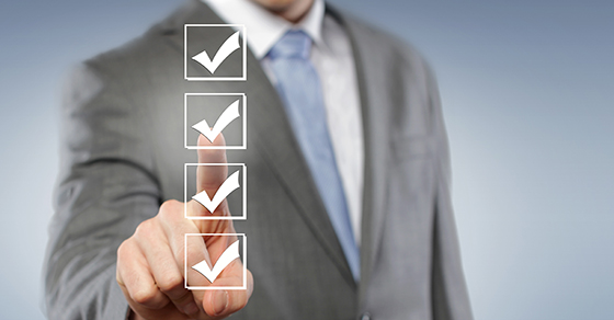 Man in business suit pointing at checkmarks in a list