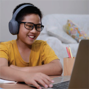 Boy using laptop computer with headphones on