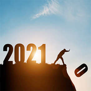 Man pushing the number zero off cliff with the numbers 2021 behind him with sun in background