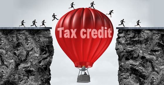 Red hot air balloon with words tax credit between two cliffs with people running over the top