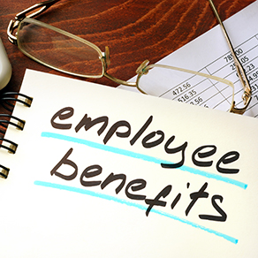 Employee benefits written on a notepad with a pair of glasses lying next to the notepad