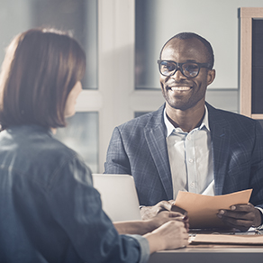 Business man and woman sitting across table from one another in job interview