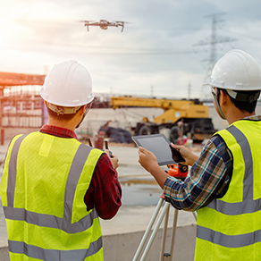 Two construction worker on building site, operating a drone and digital construction technology.