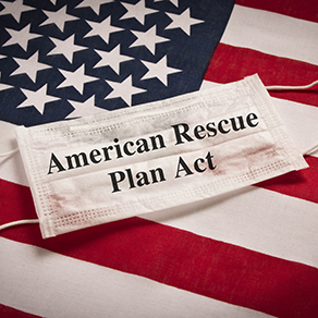 Protective medical mask on the background of the American flag and the caption of American Rescue Plan Act on the mask.