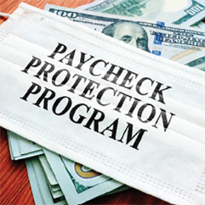 Medical mask with Paycheck Protection Program written on it sitting on top of $100 dollar bills