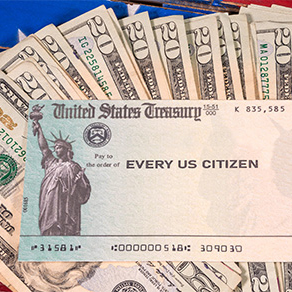 Stack of twenty dollar bills fanned out with a check from the US treasury payable to every US citizen
