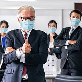 Confident business people with face mask protect from Coronavirus or COVID-19. Concept of help, support and collaboration together to overcome epidemic of Coronavirus or COVID-19 to reopen business