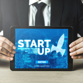 Close up of man in suit holding a tablet computer with a graphic on the screen that reads start up
