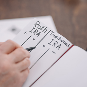 cropped view of senior hand writing in notebook with roth ira and traditional ira words