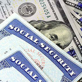 Cropped photo of two Social Security cards and 100 dollar bills representing benefits