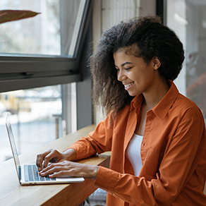 African American woman sitting at desk in front of a window working on independent contractor project