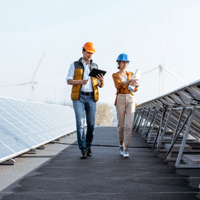 Male and Female engineers walking on roof with solar panels and windmills in the background for alternative energy
