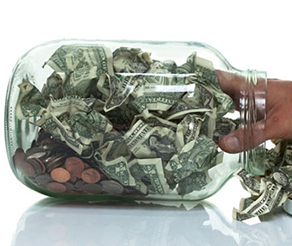 Clear jar stuffed with dollar bills and pennies and hand reaching in to grab some