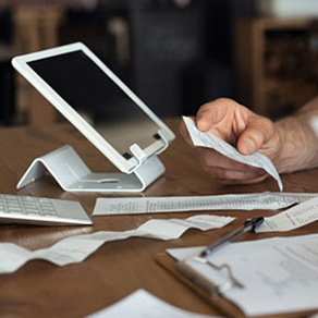 Tablet propped up surrounded by receipts and hand holding a receipt
