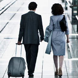Back of business man and woman walking through airport with man pulling luggage