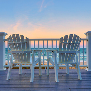 Adirondack Chairs on the deck of a vacation home looking at beach