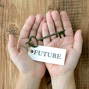 Hands cupped over a wood table holding an antiques key with a tag that reads future.