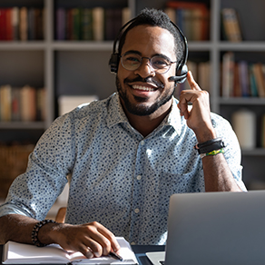 Happy young african american man wearing headset, looking at camera, remote selling.
