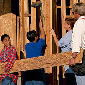 Children and adults carrying a board and working on building a housing frame