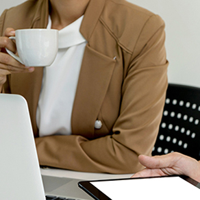 Women holding a coffee cup sitting in front of a laptop