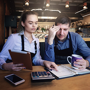 Man and woman in aprons sitting at table looking frustrated at calculator, accounting books