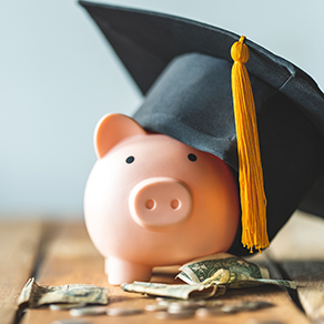 Pink piggy bank with graduation hat on and dollar bills laying next to it