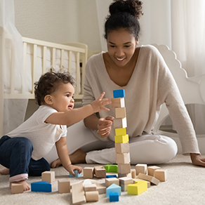 Woman in front of crib playing with blocks with baby