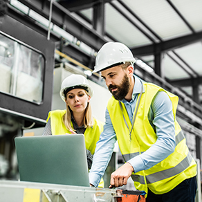 Two people in vests and hard hats looking over a laptop