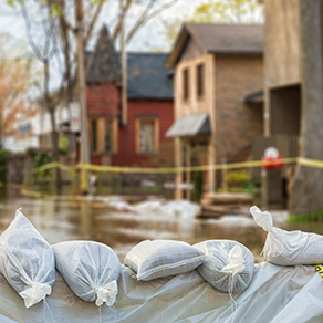 Flooded street with sandbags in front of homes