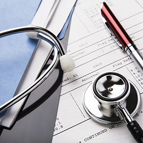 stethoscope and pen resting on a sheet of medical lab test results, with patient file and x-ray